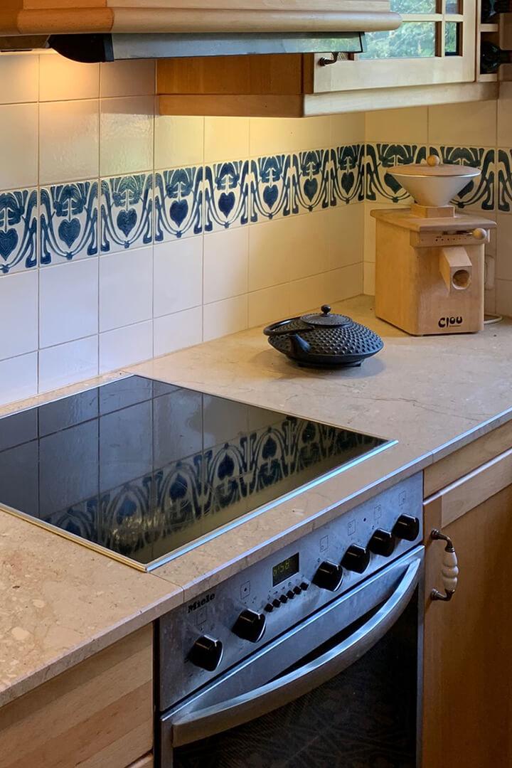 Küchenspiegel mit weißen Wandfliesen und einer Reihe von Jugendstil - Dekorfliesen