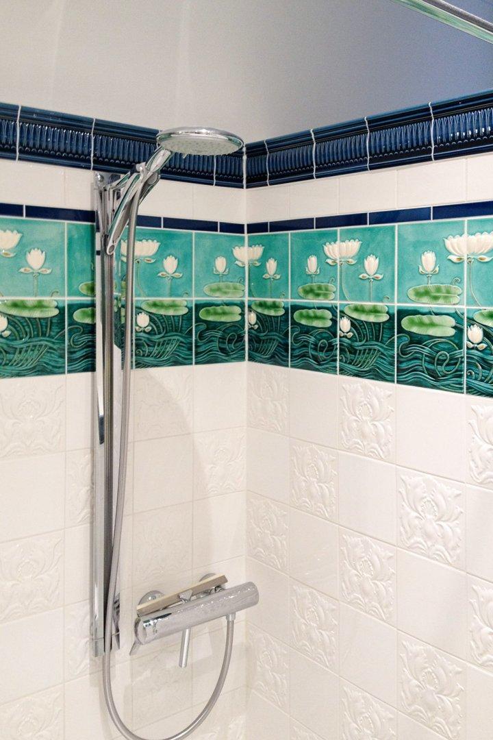 Seerosenfliese in Dusche mit blauer Bordüre. Traditionelle Badgestaltung mit alten Fliesen.