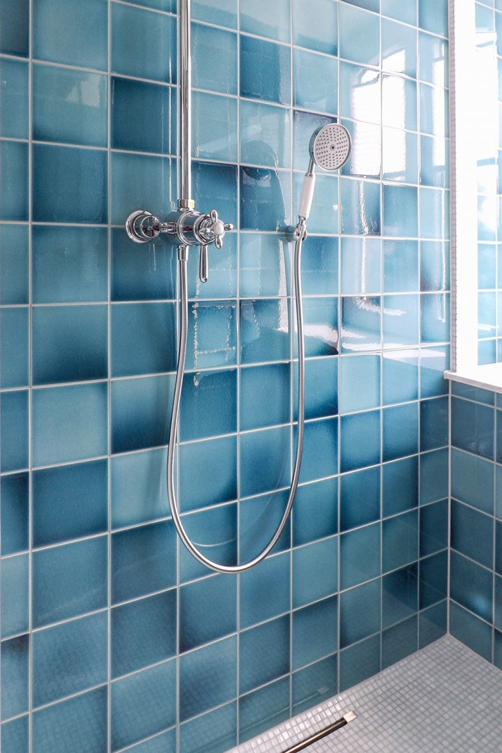 Shower in La Maison with traditional wall tiles in blue. Lively surface through color gradients.