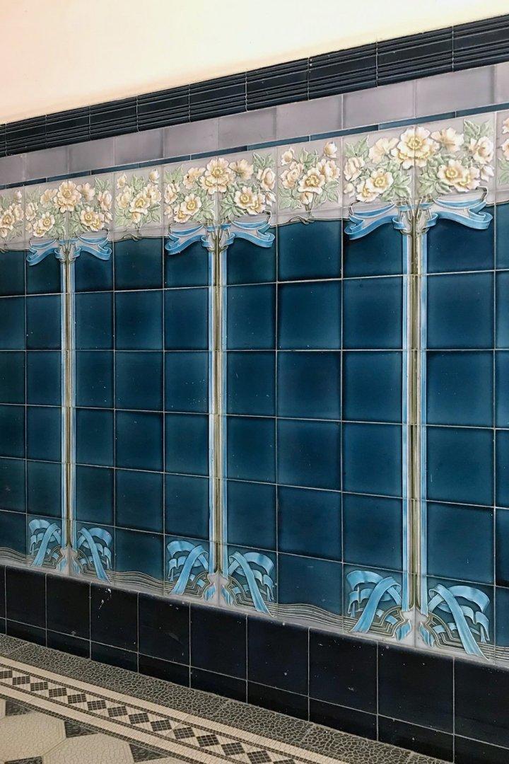 Blaues Wandfliesenornament Rosenstock. Originalverlegung als fortlaufendes Motiv.