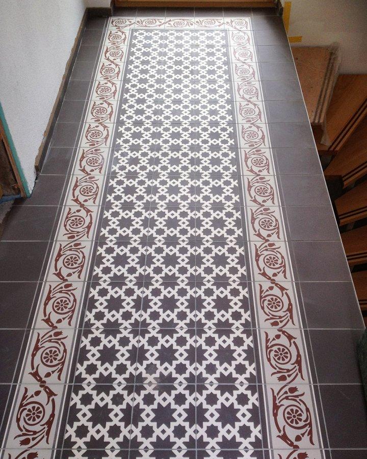 Carrelage de sol à motifs bicolores en blanc crème et brun noir avec un motif d'arabesque incrusté.