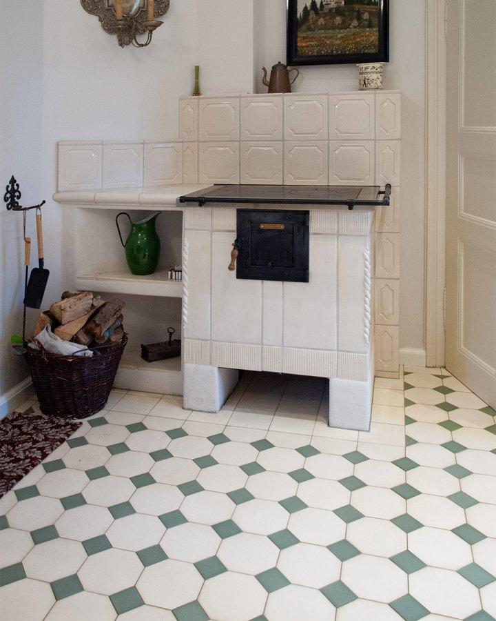 Carrelage de sol octogone blanc crème avec incrustation vert menthe. Sol carrelé classique devant la cheminée.