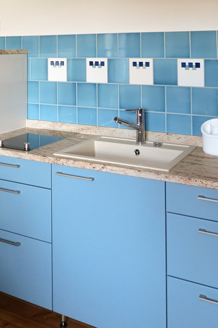 Kitchen mirror with blue gray tiles F 10.622 on the worktop.