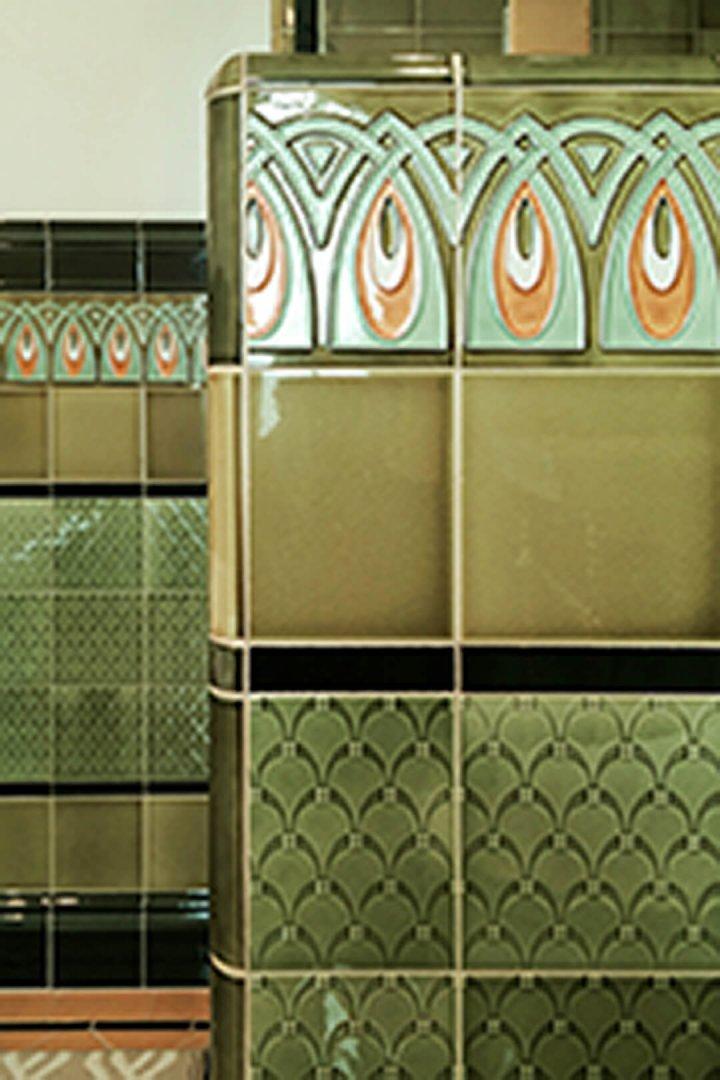 Paroi avant avec carreaux de mur vert clair et vert foncé, bordures et carreaux décoratifs.