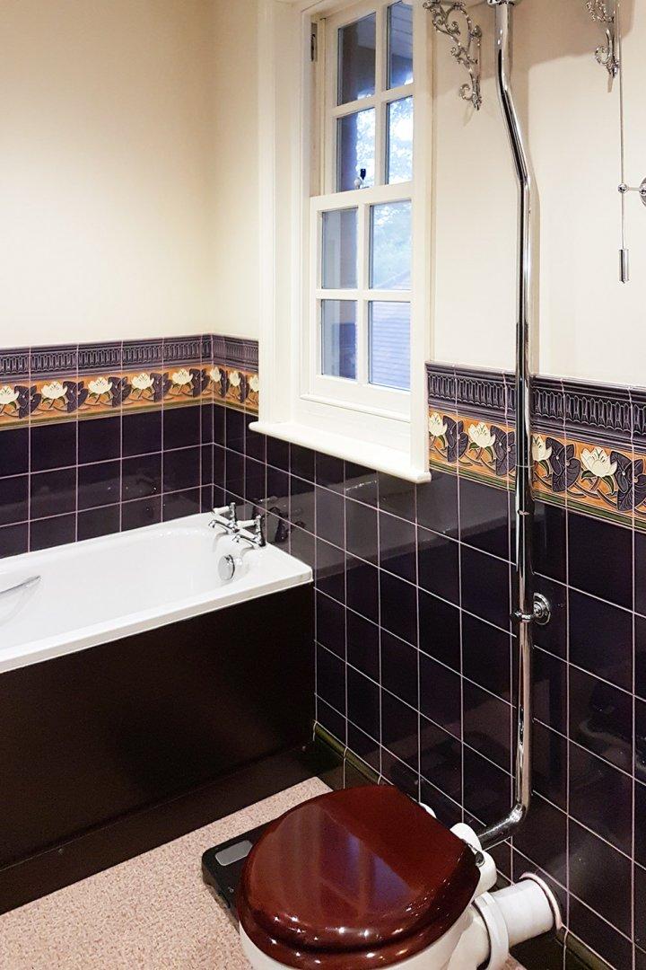Carrelage mural violet noir au format 15x15. Salle de bain équipée de façon traditionnelle.