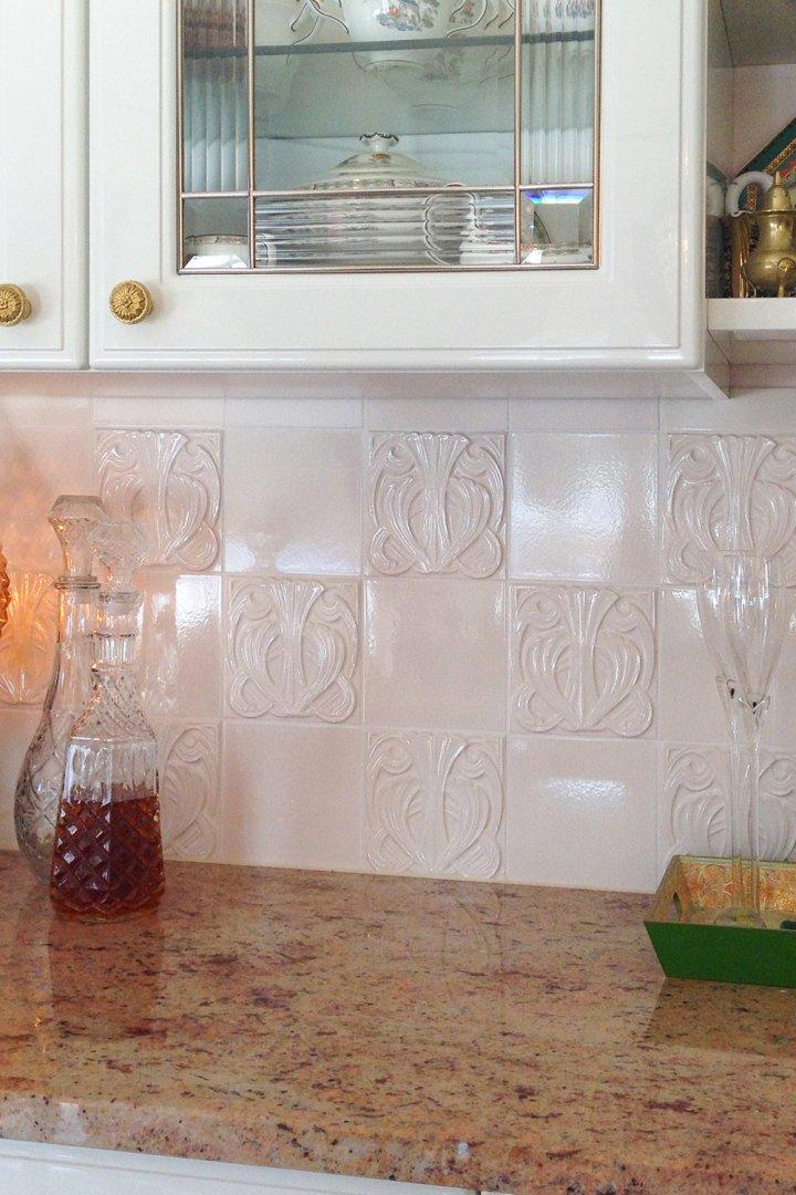 weißer Küchenspiegel mit historischer quadratischer Fliese.