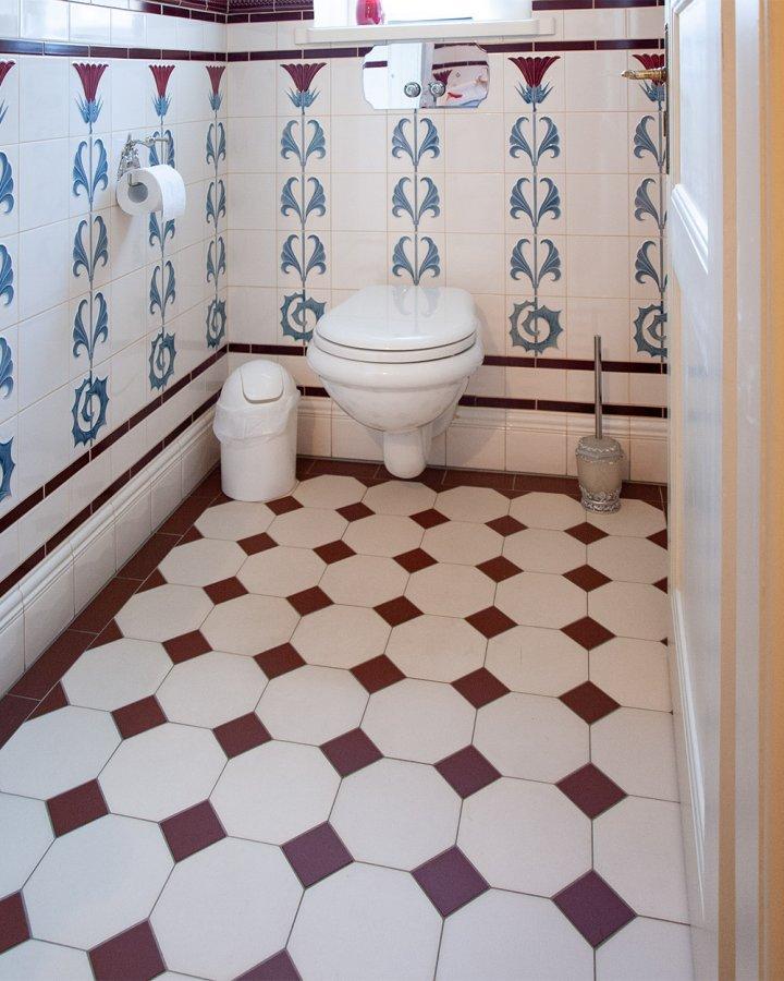 Achteck Bodenfliese cremeweiß mit rotem Einleger. Klassischer Fliesenboden im Badezimmer.