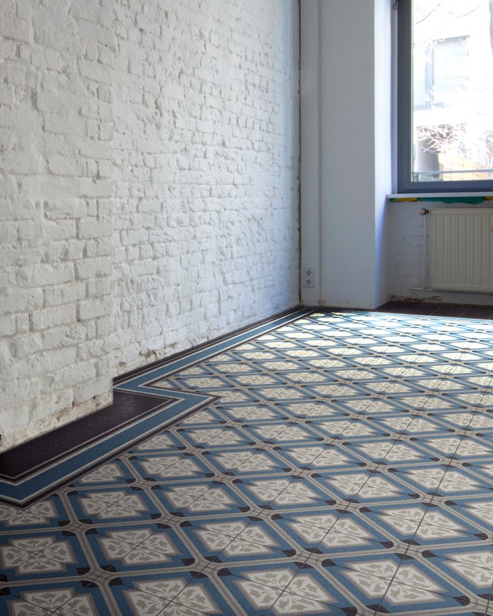 Loft apartment with old floor tiles from the Wilhelminian era or Art Nouveau. Stoneware in gray-blue and beige-gray.